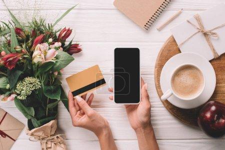 Photo pour Plan recadré de femme tenant carte de crédit et smartphone avec écran blanc sur la table avec bouquet de fleurs et tasse de café - image libre de droit