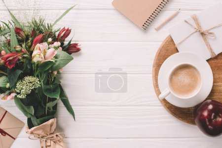 Photo for Flat lay with wrapped bouquet of flowers, cup of coffee and notebook on white wooden tabletop - Royalty Free Image