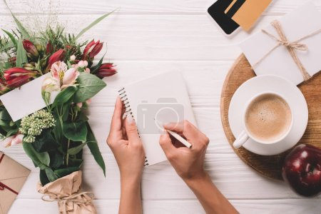 partial view of woman making notes in notebook at tabletop with bouquet of flowers and cup of coffee