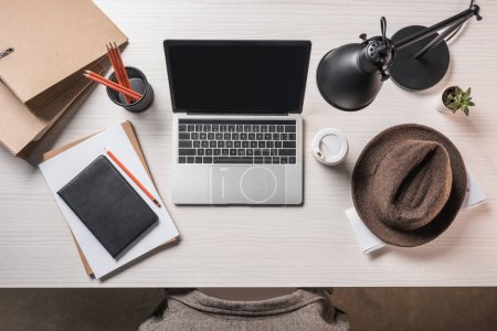 top view of laptop with blank screen, fedora hat, coffee cup and stationery on table