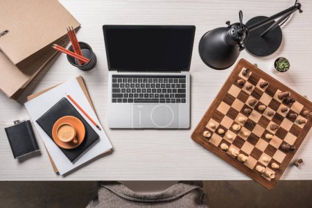 Photo for Top view of workplace with chessboard, coffee, laptop and stationery on table - Royalty Free Image