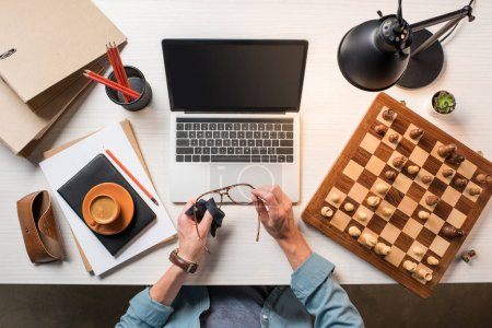 cropped image of male freelancer wiping eyeglasses at working table with laptop, chessboard and coffee