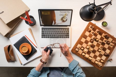 cropped image of male freelancer wiping eyeglasses at table with chessboard, coffee and laptop with tickets online on screen