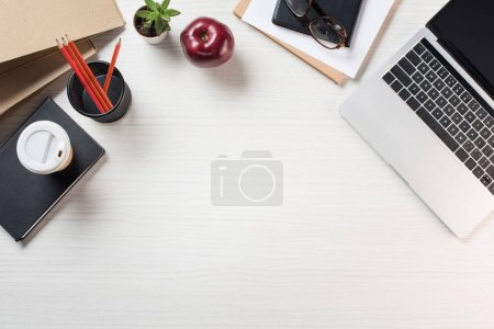 elevated view of apple, paper cup of coffee, stationery and laptop on table