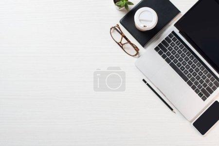vista superior del lugar de trabajo con anteojos, café y computadora portátil con pantalla en blanco en la mesa