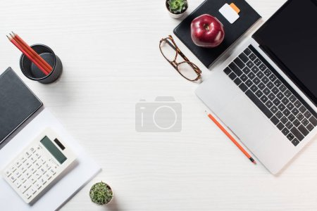 Photo for Elevated view of workplace with stationery, eyeglasses, calculator and laptop on table - Royalty Free Image