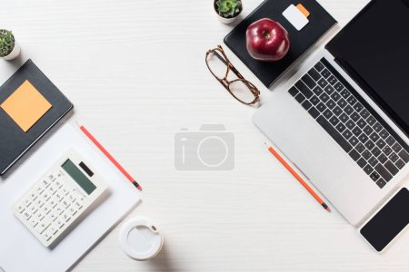 top view of workplace with calculator, stationery, coffee and digital devices on table