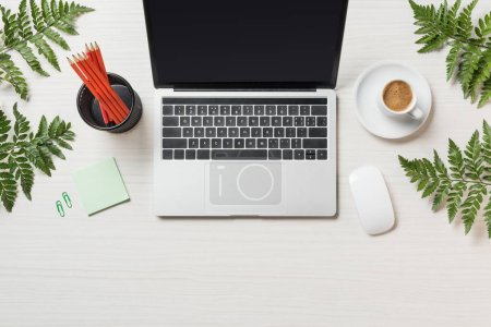 Photo for Top view of workplace with laptop, computer mouse, coffee and stationery surrounded by fern leaves - Royalty Free Image