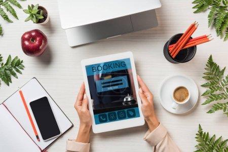 Foto de Imagen recortada de mujer independiente con tableta digital con reserva en pantalla en la mesa con los gadgets y café rodeado de hojas de helecho - Imagen libre de derechos