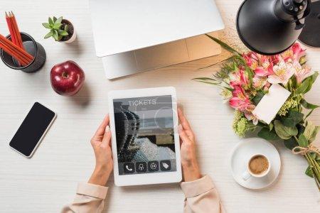 Photo pour Cropped image de pigiste femme tenant une tablette numérique avec des billets sur écran à table avec une tasse de café, gadgets et fleurs avec carte de voeux - image libre de droit