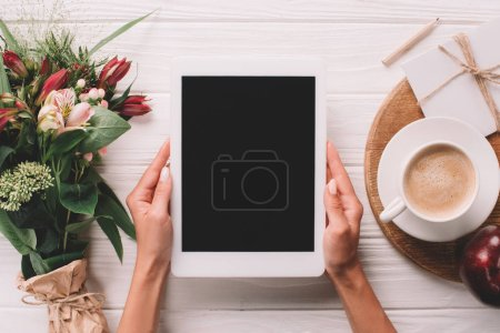 partial view of woman holding tablet with blank screen at surface with wrapped bouquet of flowers and cup of coffee