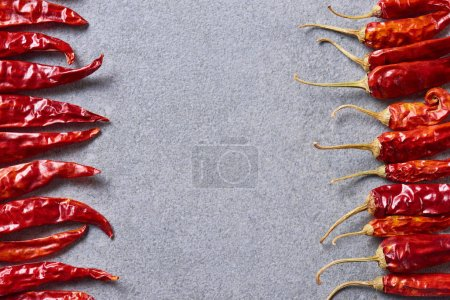 Photo for Top view of red chili peppers arranged on grey tabletop - Royalty Free Image