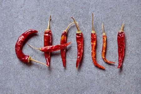 top view of chili peppers arranged in chilli lettering on grey tabletop