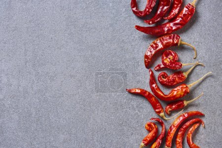 top view of red dried chili peppers arranged on grey tabletop