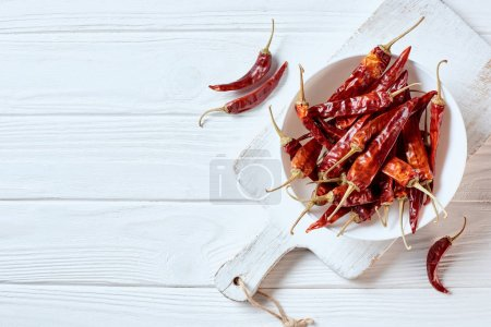 top view of dried cayenne peppers in bowl on white cutting board on wooden surface
