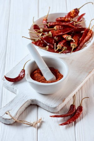 close up view of grinded chili pepper in mortar with pestle on white wooden surface