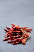 close up view of pile of red chili peppers on grey surface