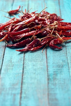 close up view of red dried chili peppers on blue wooden surface
