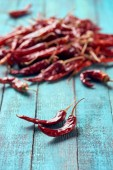 close up view of dried chili peppers on blue wooden surface
