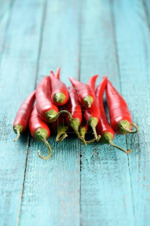 Photo for Red ripe chili peppers on blue table - Royalty Free Image