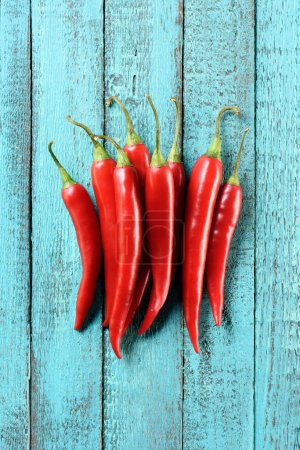 top view of pile of red ripe chili peppers on blue wooden table