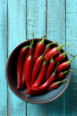 top view of red ripe chili peppers in bowl on blue wooden table