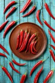top view of red ripe chili peppers on plate and blue wooden table