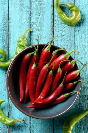 top view of red chili peppers in bowl and scattered green peppers on blue wooden table