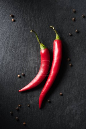 top view of two ripe chili peppers on black surface