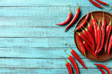 elevated view of red ripe chili peppers on plate and blue wooden table