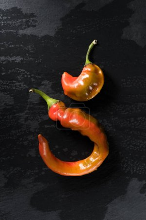 top view of two chili peppers on black surface
