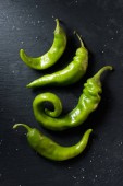 top view of green ripe chili peppers on black surface