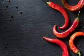 elevated view of red organic chili peppers on black surface