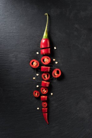 Photo for Elevated view of cut red ripe chili pepper on black surface - Royalty Free Image