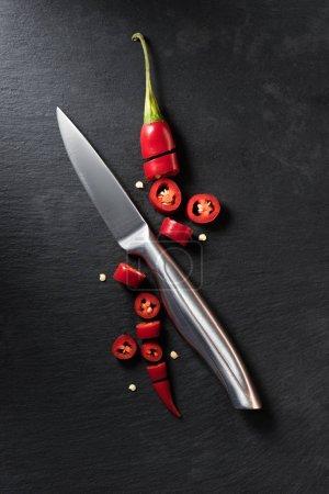erhöhte Ansicht von geschnittener roter reifer Chilischote und Messer auf schwarzer Oberfläche