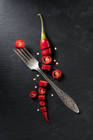 elevated view of cut red ripe chili pepper and fork on black surface