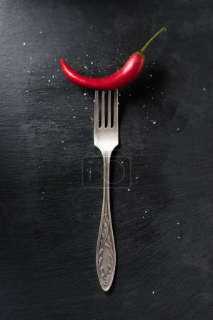 Photo for Top view of red ripe chili pepper and fork on black surface - Royalty Free Image