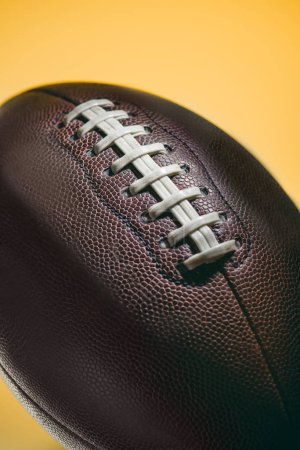 close up of brown american football ball isolated on yellow