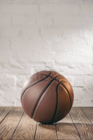 one brown basketball ball on wooden floor