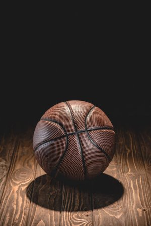 one brown basketball ball on wooden floor in dark room