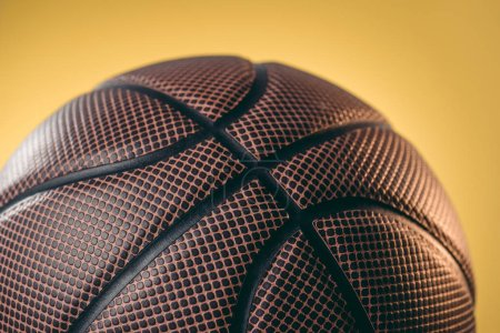 close up of brown basketball ball isolated on yellow