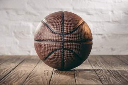 Photo for Brown leather basketball ball on wooden floor - Royalty Free Image