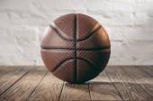 """Постер, картина, фотообои """"коричневый кожаный мяч баскетбол на деревянном полу"""""""