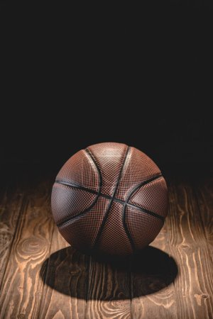 one rubber basketball ball on wooden floor in dark room