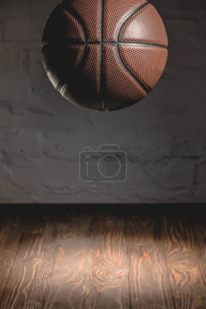 brown basketball ball falling on wooden floor
