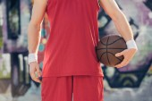 cropped image of basketball player standing with basketball ball on street