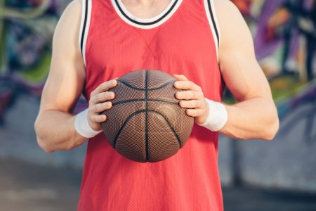 cropped image of basketball player holding basketball ball on street