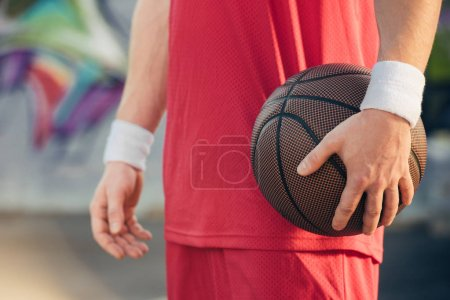 cropped image of basketball player in red sportswear holding basketball ball on street