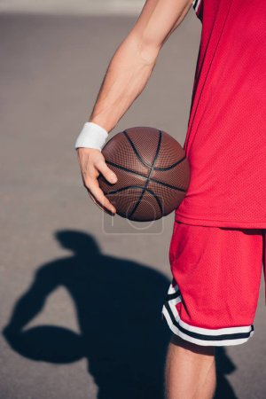 cropped image of sportsman holding basketball ball on street