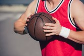 cropped image of sportsman playing basketball on street